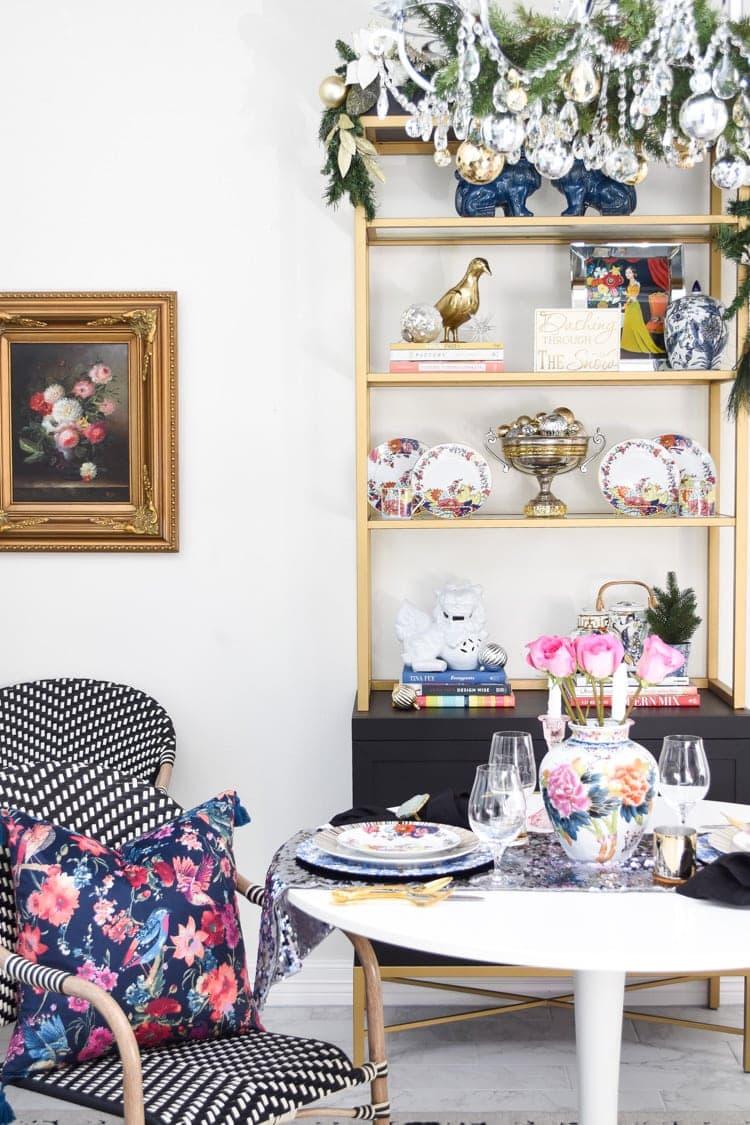 Black and gold bookcase in a dining room with antique finds