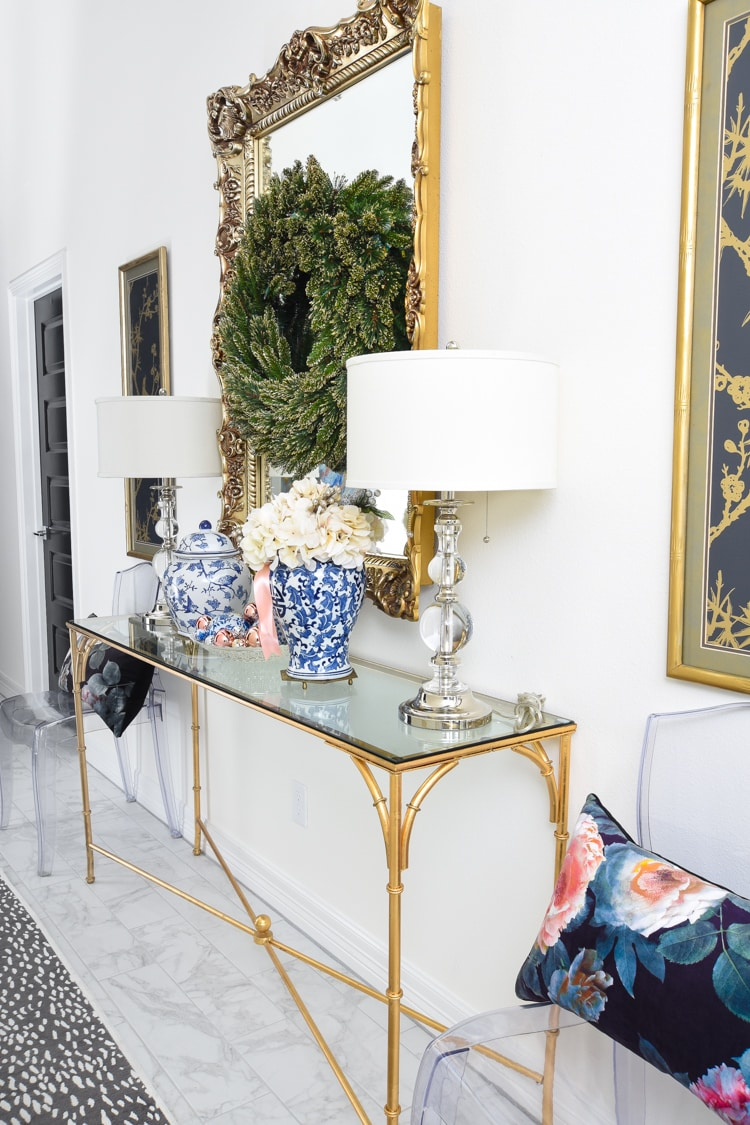 White foyer with gold mirror and ginger jars