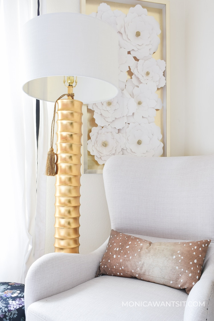 Gold bamboo floor lamp and floral artwork
