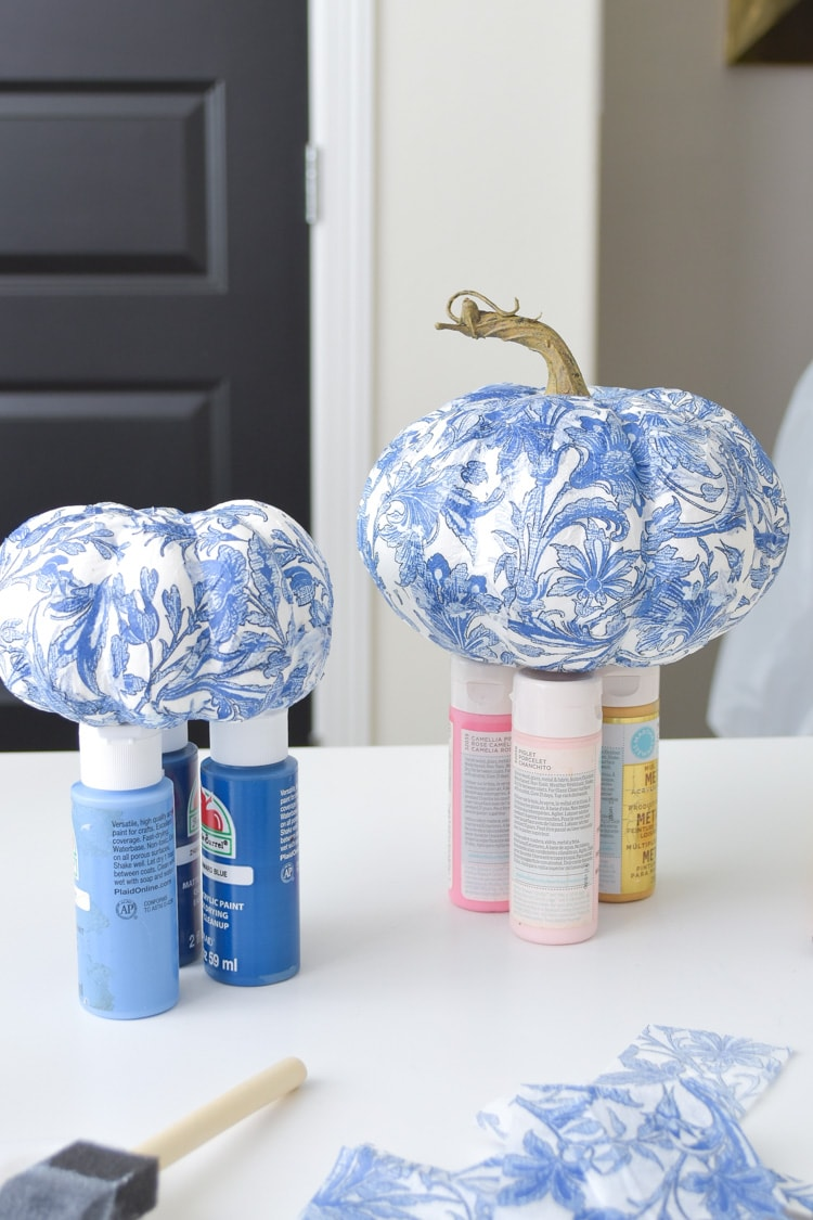 Mod podge pumpkins with blue and white chinoiserie napkins drying for fall decor