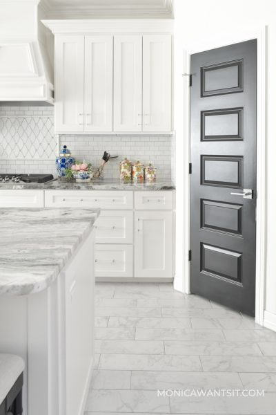 Traditional white kitchen with marble floors and black interior pantry door