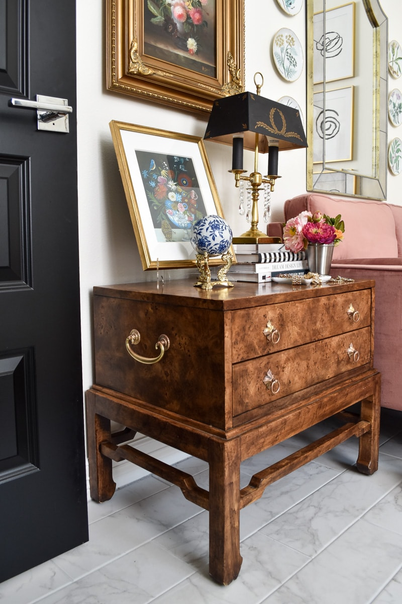 Vintage and thrifted burl wood nightstand table in a home office with a blush pink velvet loveseat.